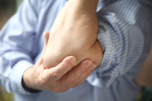 Man holding painful elbow Tendonitis