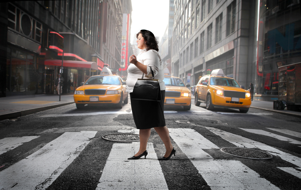 Obese business woman walking across a city street